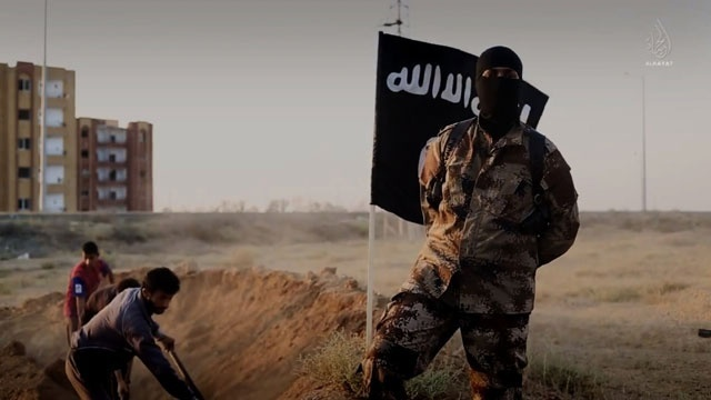 ISIS fighter in front of black flag_2652852052682929