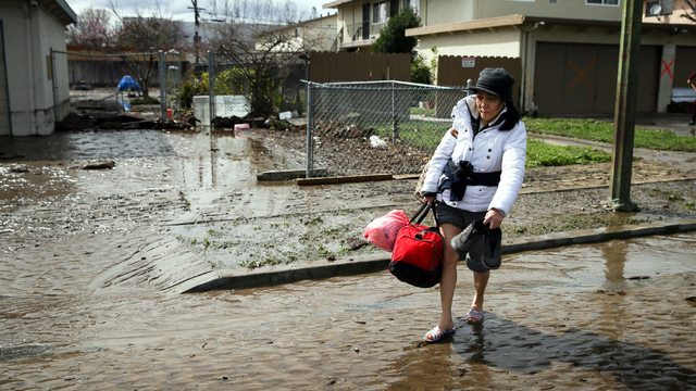 San Jose flood woman walks in mud.jpg67219226
