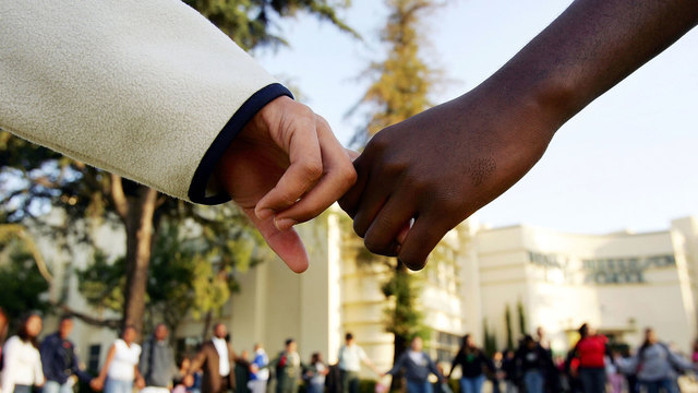 white and black students holding hands50214258