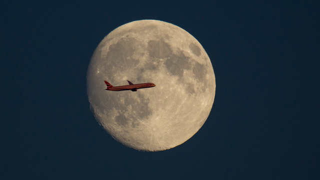 Plane flies past the moon.jpg01814006